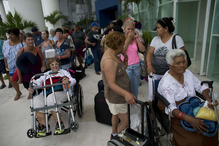 Mexican and international tourists wait at a conference center to be transferred to a shelter, ahead of the arrival of Category 5 Hurricane Patricia in Puerto Vallarta, Mexico, Friday, Oct. 23, 2015. Teams of police and civil protection are walking along Puerto Vallarta's waterfront Friday morning advising people to evacuate. A top civil protection official says that three airports in the path of Patricia in southwestern Mexico have been shut down as the storm approaches. (AP Photo/Rebecca Blackwell) Photo: Rebecca Blackwell, Associated Press