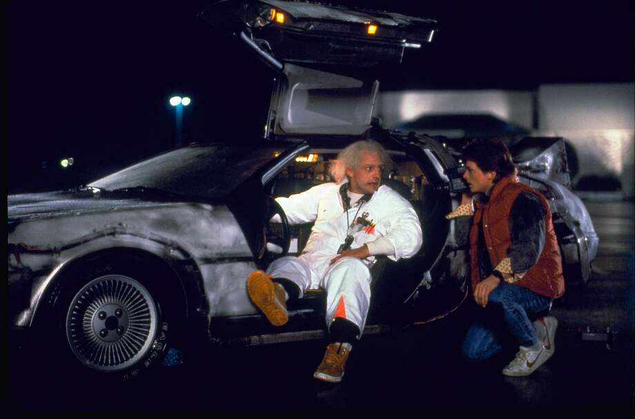 """Christopher Lloyd (left) as Dr. Emmett Brown, Michael J. Fox as Marty McFly and a DeLorean in the 1985 film, """"Back to the Future."""" Photo: Associated Press"""