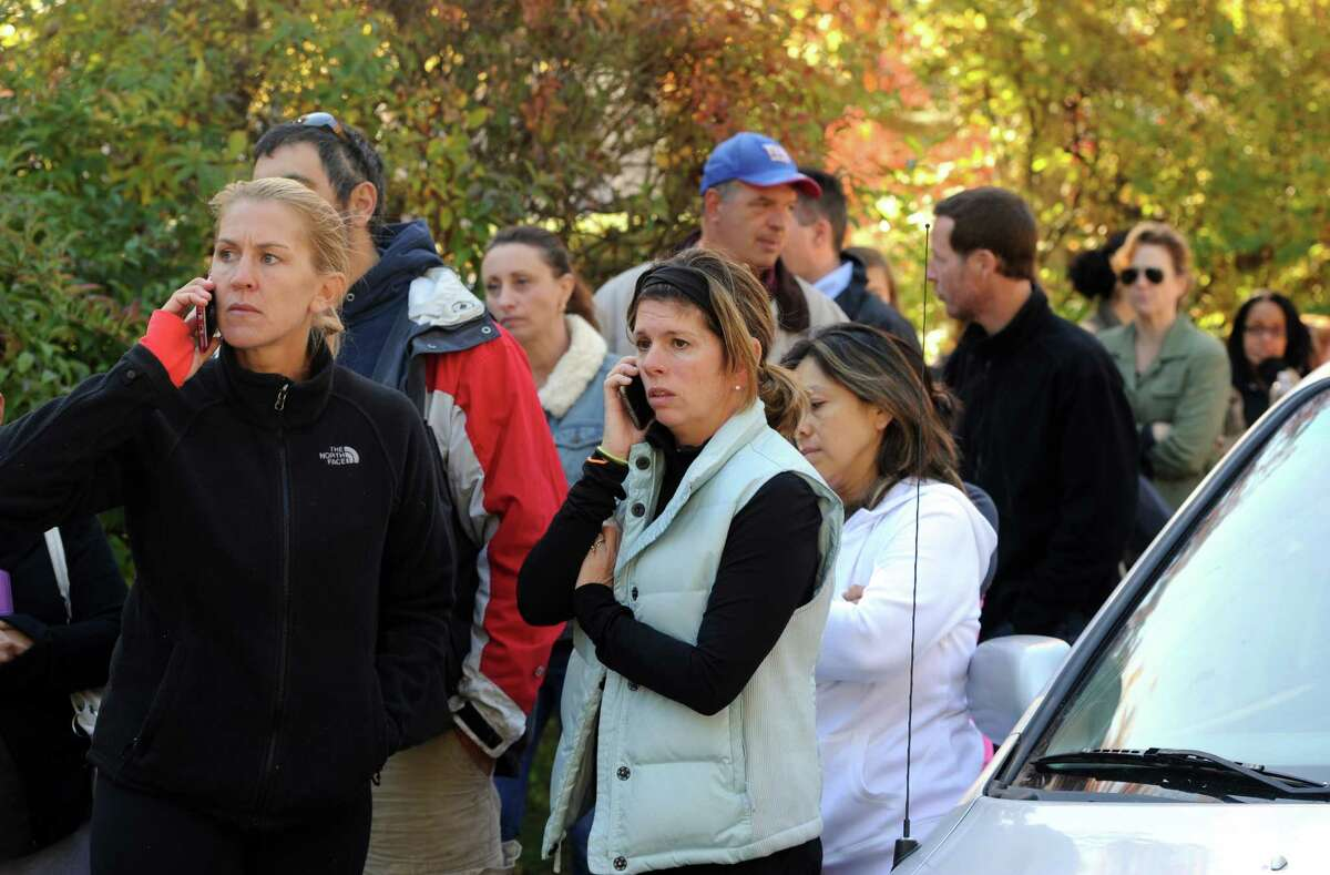 Parents gather at Holland Hill School in Fairfield, Conn. to get information and to pick up their children after a threat forced the school into lockdown on Friday, Oct. 23, 2015. All Fairfield schools were dismissed early after several phoned threats prompted a lockdown of all 17 public school buildings.