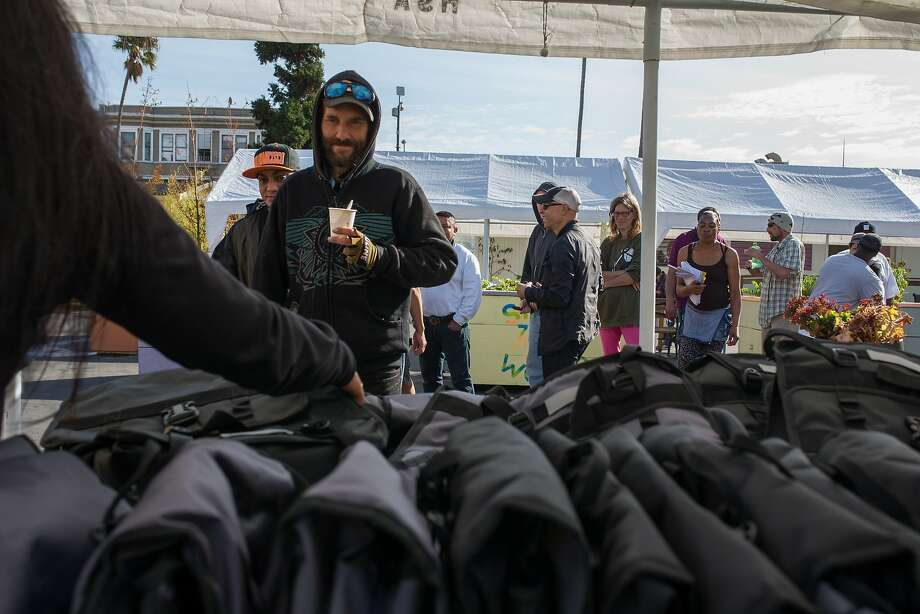 People line up at the Navigation Center on Mission Street near 16th in San Francisco to receive Citypaks specially designed for the homeless by Chicago philanthropist Ron Kaplan, who was on hand for the distribution. Photo: Nathaniel Y. Downes, The Chronicle