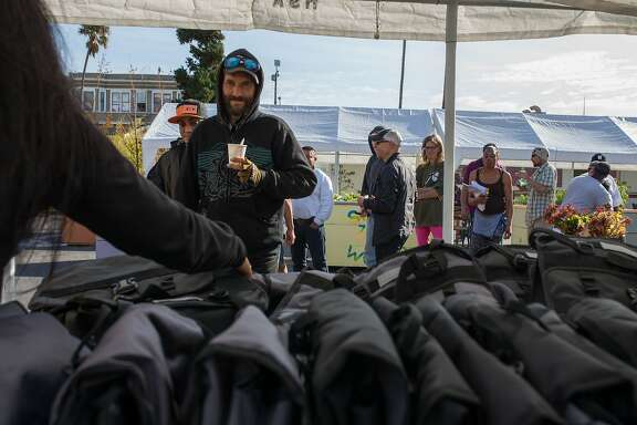 Residents of the homeless Navigation Center in the Mission district line up to receive a free backpack on Friday, Oct. 23, 2015 in San Francisco, Calif.  Chicago philanthropist, Ron Kaplan, gives away backpacks created with specific homeless needs in mind (security straps, rain poncho and reflective webbing).