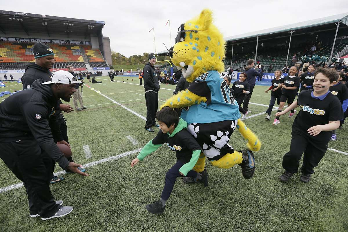 Jacksonville Jaguars players and the mascot take part in community day activities with local schoolchildren following a training session at Allianz Park in London, Friday Oct. 23, 2015. The Jaguars are preparing for an NFL football game against the Buffalo Bills at London's Wembley stadium on Sunday. (AP Photo/Tim Ireland)