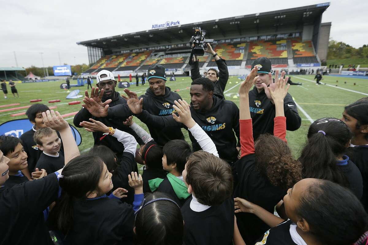 Jacksonville Jaguars players take part in community day activities with local schoolchildren following a training session at Allianz Park in London, Friday Oct. 23, 2015. The Jaguars are preparing for an NFL football game against the Buffalo Bills at London's Wembley stadium on Sunday. (AP Photo/Tim Ireland)