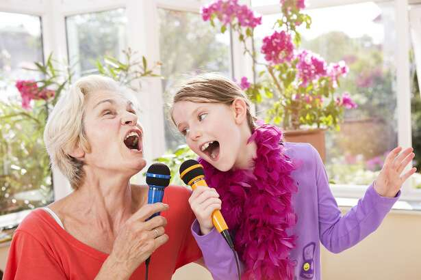 Grandmother and grandchild singing karaoke.