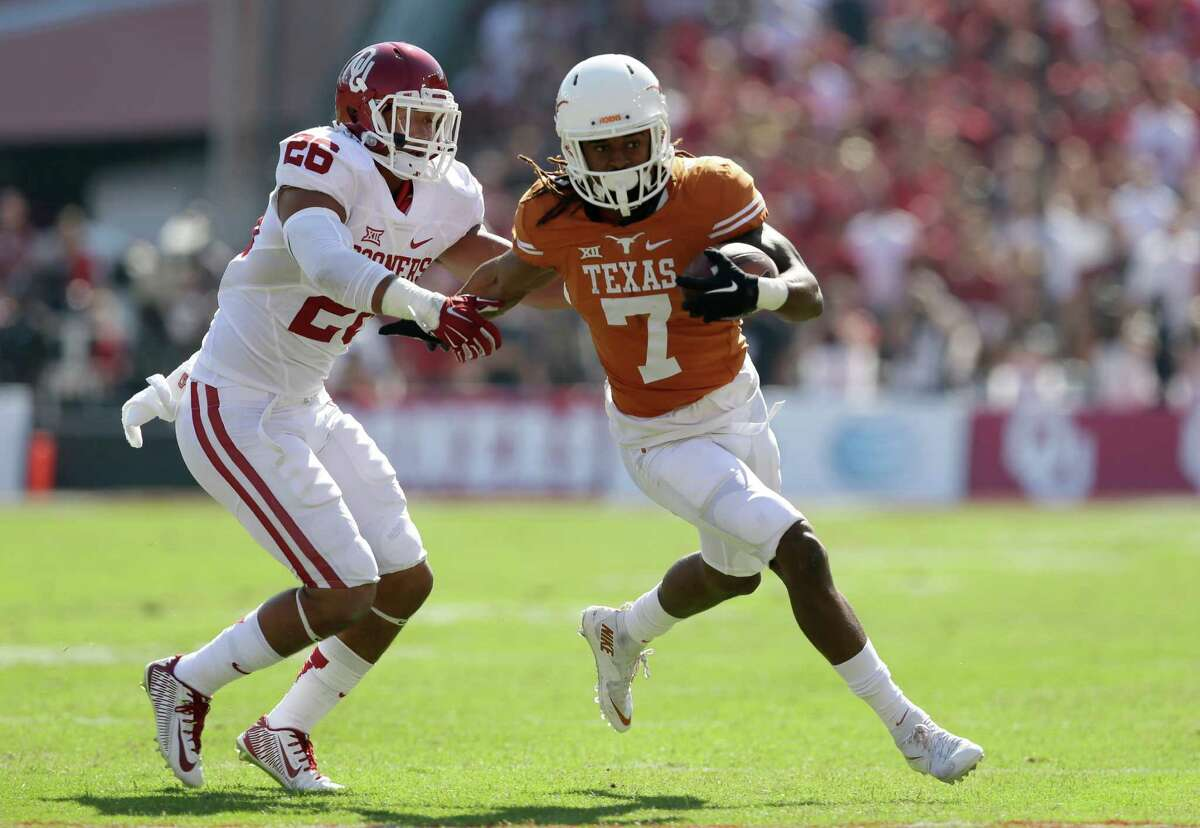 Oklahoma linebacker Jordan Evans (26) attempts to bring down Texas wide receiver Marcus Johnson (7) in the first half of an NCAA college football game Saturday, Oct. 10, 2015, in Dallas. (AP Photo/LM Otero)