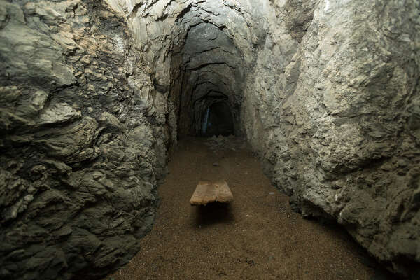 A wooden plank is buried under sand, deposited over decades of high tides washing into the cave.