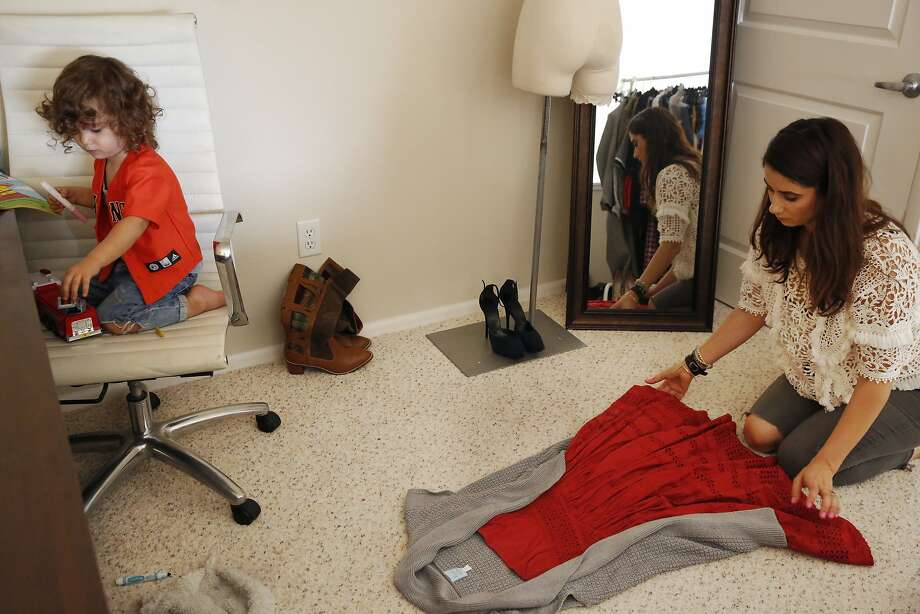 """Savannah Sarkisian-Barrozo, 29, lays out an outfit for a photograph as her son Royce Barrozo, 2, plays nearby at her home Oct. 23, 2015 in Emeryville, Calif. Sarkisian-Barrozo works 60-80 hour weeks from home buying and selling clothing through an app called Poshmark. Her business is called """"Curated Resale"""" and her handle is 3bugmama. Photo: Leah Millis, The Chronicle"""