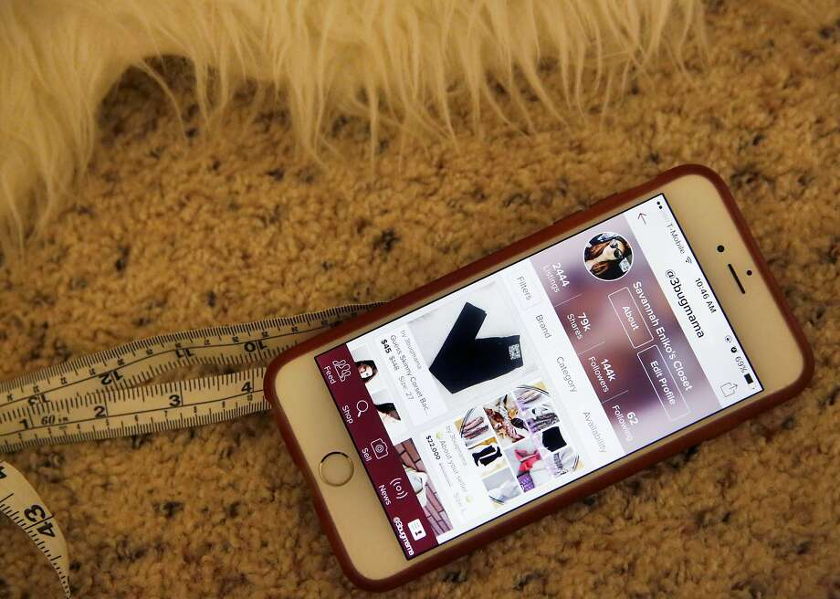 """The homepage for Savannah Sarkisian-Barrozo, 29, on the Poshmark app can be seen on her phone as she posts new items at her home Oct. 23, 2015 in Emeryville, Calif. Sarkisian-Barrozo works 60-80 hour weeks from home buying and selling clothing through an app called Poshmark. Her business is called """"Curated Resale"""" and her handle is 3bugmama. Photo: Leah Millis, The Chronicle"""