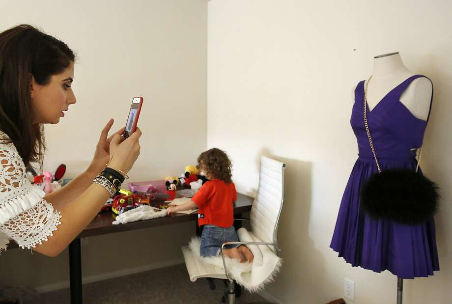 Savannah Sarkisian-Barrozo, 29, photographs a dress as her son Royce Barrozo, 2, plays in the background at her home Oct. 23, 2015 in Emeryville, Calif. Sarkisian-Barrozo works 60-80 hour weeks from home buying and selling clothing through an app called Poshmark. Her business is called