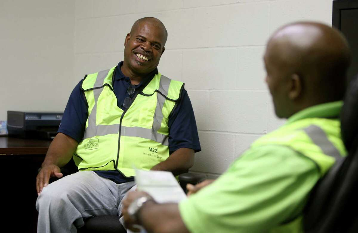 Dwight Townsend, left, shown with Jerome White, roll off route manager, accepts an offer for a roll off driver position at the Waste Management National Career Day, to recruit truck drivers and technicians, Wednesday, Oct. 21, 2015, in Houston, Texas. ( Gary Coronado / Houston Chronicle )