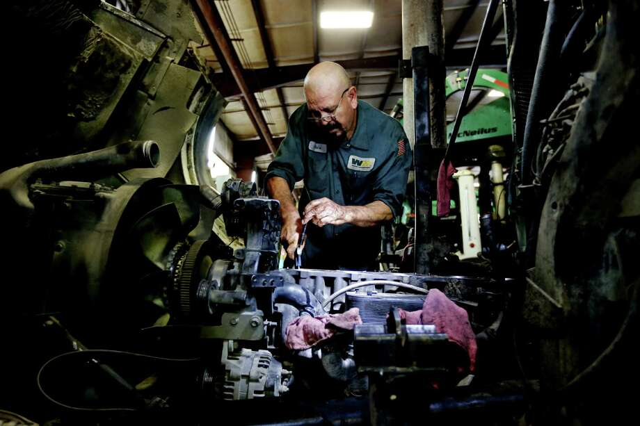 Javier Martinez, a technician, works on a garbage truck's diesel engine at the Waste Management facility on Todd Road. Waste Management this week held its national career day to recruit truck drivers and technicians. Photo: Gary Coronado, Staff / © 2015 Houston Chronicle