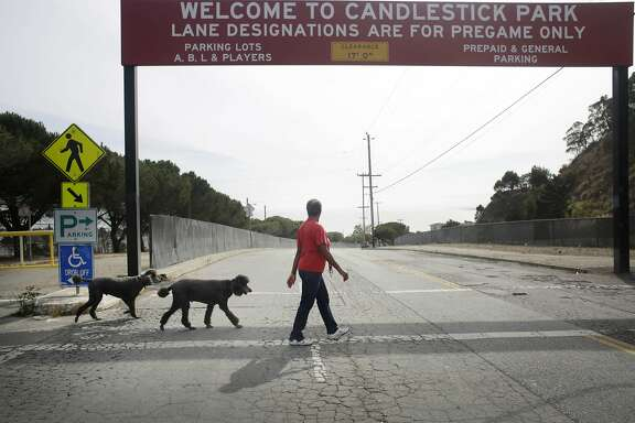 Shirley Moore, member of the Bayview Hill Neighborhood Association, Candlestick Point Neighborhood Committee chair and Clear Air Health Alliance president, walks her dog along Jamestown Avenue  on Friday, October 23,  2015 in San Francisco, Calif.