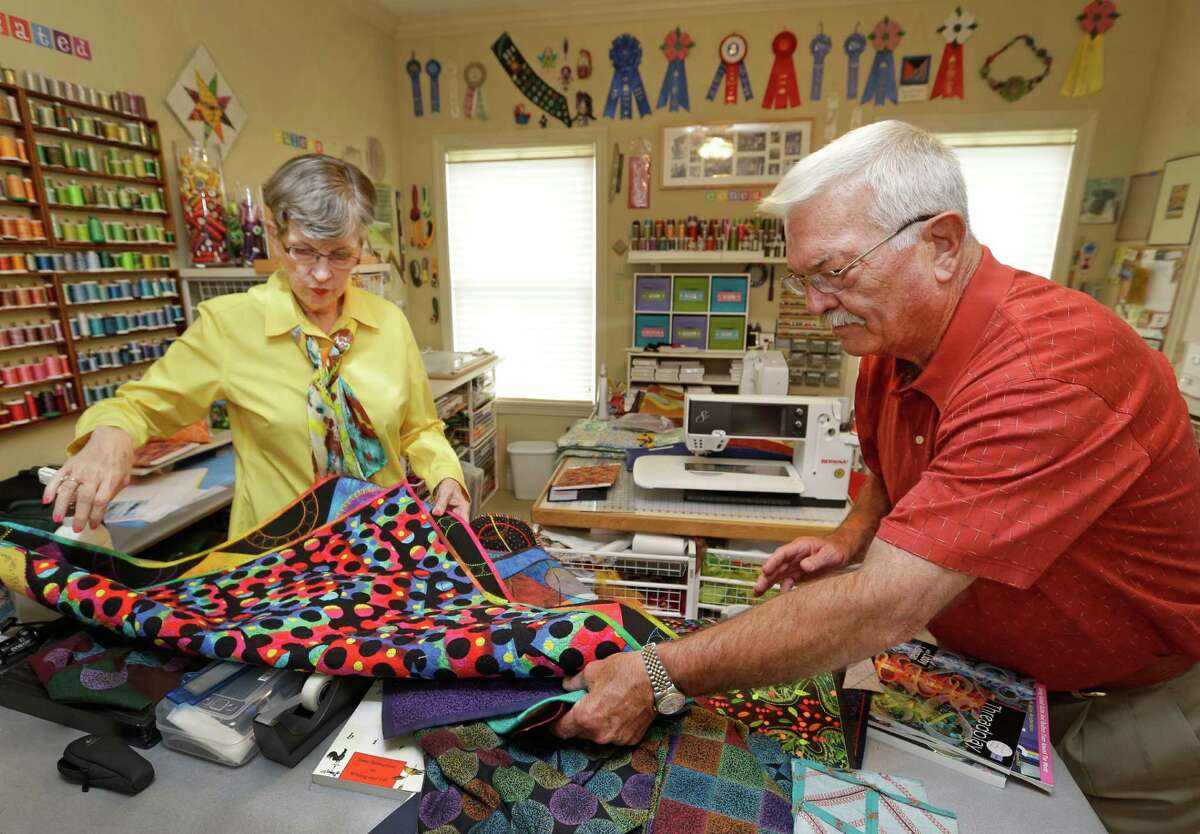 Libby Lehman and her husband, Lester Lehman, look through a stack of quilts in her home studio. She was a leader in her field until she was stopped by a brain aneurysm and stroke two years ago.