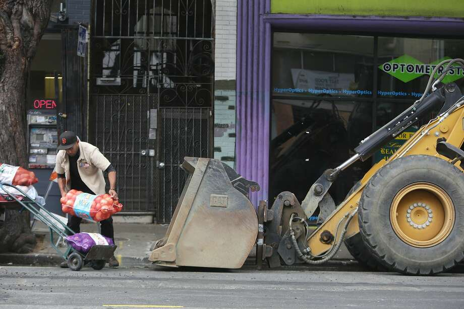 Sam Afuhaamango of Manu Produce picks up a bag of produce that had tipped over as he loads a dolly with produce next to construction equipment not being used during a delivery on Haight Street between Masonic and Ashbury on Friday, October 23,  2015 in San Francisco, Calif. Photo: Lea Suzuki, The Chronicle