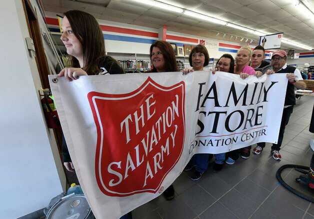 Staff members carry the temporary sign to the front of the building as final preparations are being made for the grand opening on Saturday of the Salvation Army Family Store Friday Oct. 23, 2015 in Clifton Park, N.Y.    (Skip Dickstein/Times Union) Photo: SKIP DICKSTEIN / 10033916A