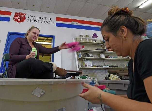 Ciara James, left and Bianca Moreno put the prices on items as preparations are being made for the grand opening on Saturday of the Salvation Army Family Store Friday Oct. 23, 2015 in Clifton Park, N.Y.    (Skip Dickstein/Times Union) Photo: SKIP DICKSTEIN / 10033916A