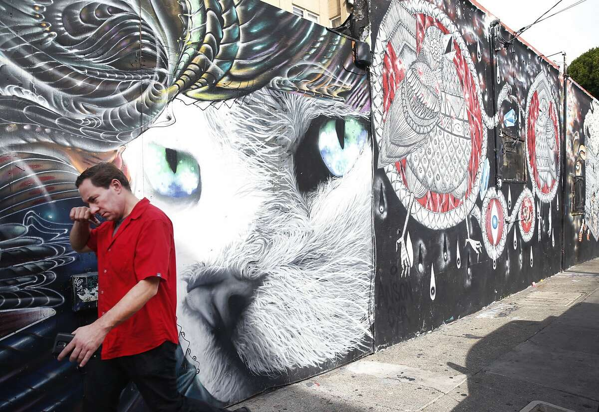 A man walks past one of the many murals on Sycamore Street in San Francisco.