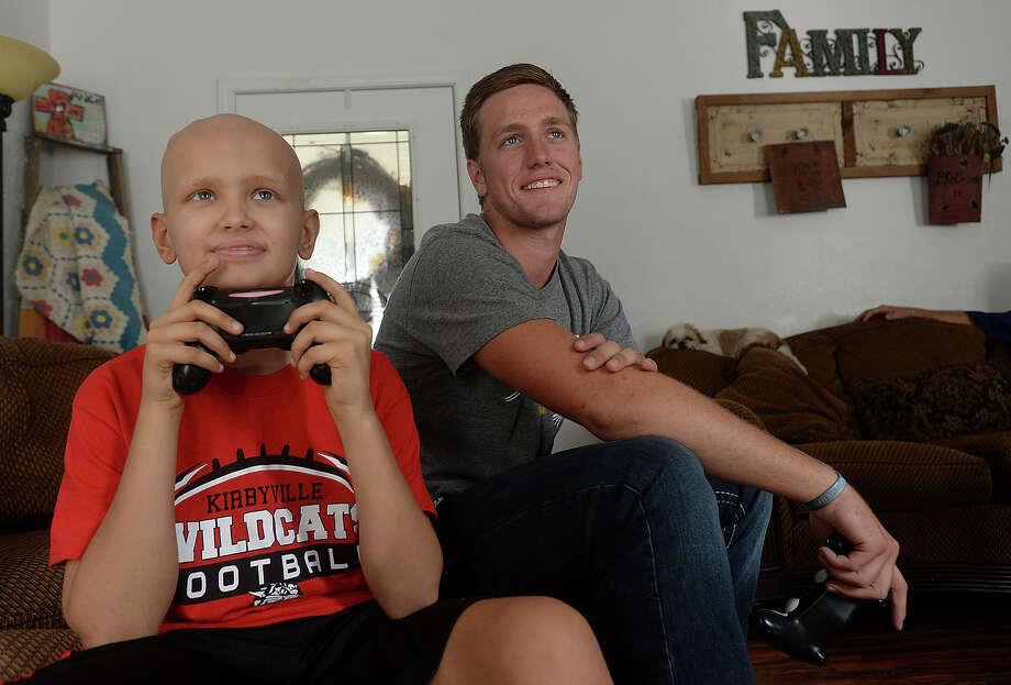 Jackson Gore may be a star on the field in his role as quarterback for the Kirbyville Wildcats, but at home, he has his hands full competing with younger brother Ty, 10, on the virtual game field playing Madden. The pair share a love of sports, and though Ty's activities are scaled down since beginning treatment for a form of brain cancer, he still makes it out to watch Jackson's games.  Photo taken Thursday, October 22, 2015 Kim Brent/The Enterprise Photo: Kim Brent / Beaumont Enterprise