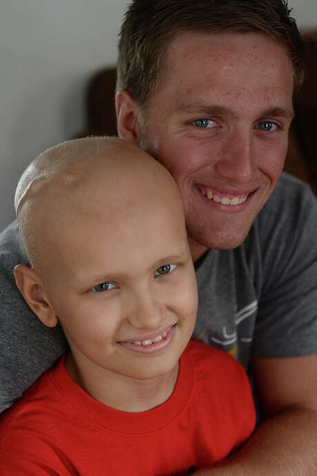 Ty Gore, 10, and his brother Kirbyville quarterback Jackson Gore are very close and share a love of sports. Though Ty's activities are scaled down since beginning treatment for a form of brain cancer, he still makes it out to watch Jackson's games.  Photo taken Thursday, October 22, 2015 Kim Brent/The Enterprise Photo: Kim Brent / Beaumont Enterprise