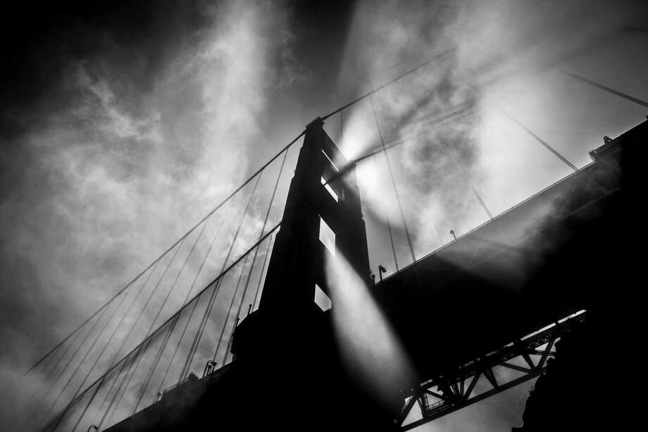 Afternoon light streams through fog blowing by the north tower of the Golden Gate Bridge in May 2012. Photo: Russell Yip / Russell Yip / The Chronicle 2012 / ONLINE_YES