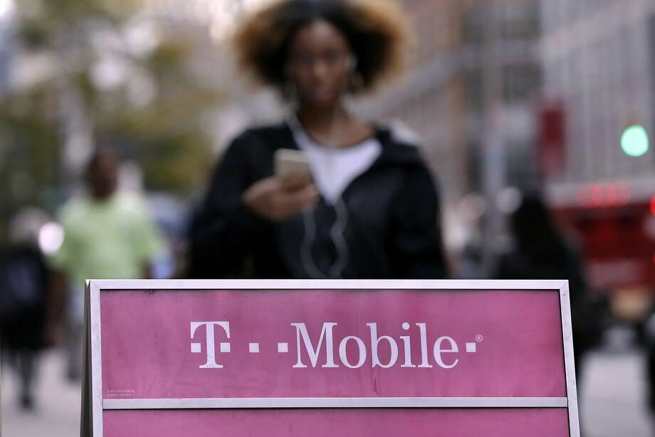 People pass a T-Mobile store, in New York,  Wednesday, Oct. 14, 2015. The top Democrat on the Senate Banking Committee is calling for the credit agency Experian to disclose more details about a data breach in which personal information on millions of T-Mobile customers was stolen. (AP Photo/Richard Drew) Photo: Richard Drew, Associated Press