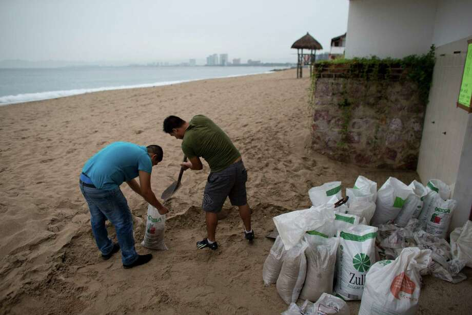 Men fill bags with sand Friday as they prepare for the arrival of Hurricane Patricia in Puerto Vallarta, Mexico. The monster Category 5 storm made landfall Friday evening with sustained winds of 165 mph. Photo: Rebecca Blackwell, STF / AP