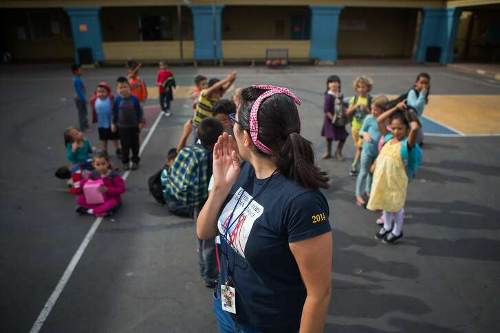 Maribel Chavez, a teacher at Buena Vista Horace Mann grade school in the Mission district, calls her students to come to class after lunchtime recess on Friday, Oct. 23, 2015 in San Francisco, Calif.