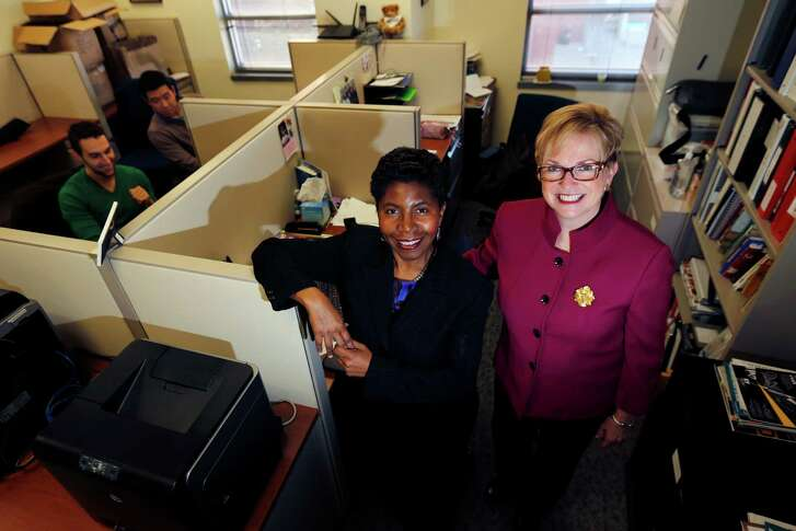 In this photo taken Friday, Consultants 2 Go co-owners Sandi Webster, center, and Peggy McHale, right, pose their office in Newark, New Jersey. The compnay, which has almost 100 employees, hired a human resources executive this year to do the research into health insurance plans. Webster and McHale want to give their staffers good insurance, but are worried about the cost.