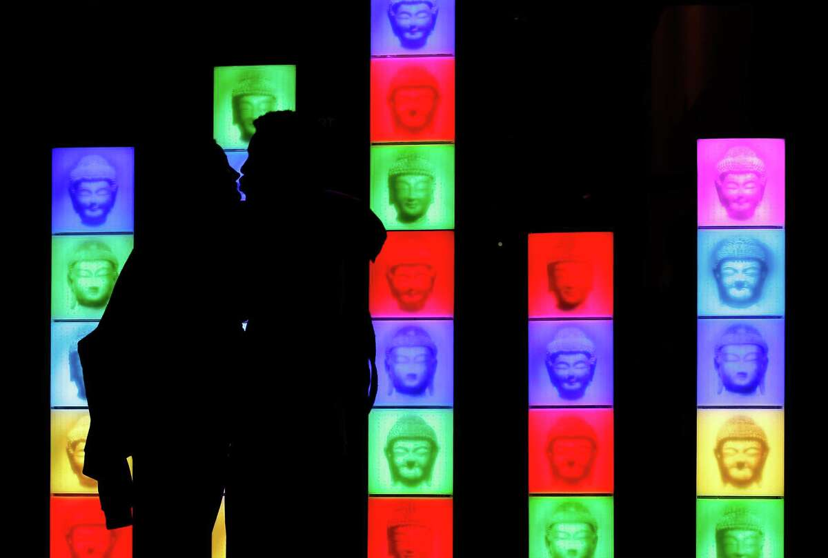 Jimmie Sutton and Marlene Wetherington kiss in front of an art display at the San Antonio Museum of Art on the first night of Luminaria in the River North neighborhood. Some outdoor events had to be canceled because of the rain.