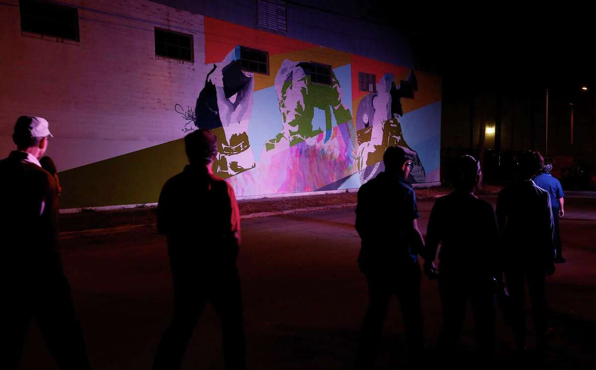 People walk past a mural by SCOTCH! on the first night of Luminaria Contemporary Arts Festival in the River North Neighborhood on Friday, Oct. 23, 2015. Despite the imminent threat of rain and storms, art patrons and a curious crowd ventured into the night to appreciate artwork spread throughout several blocks near the San Antonio Museum of Art. (Kin Man Hui/San Antonio Express-News)