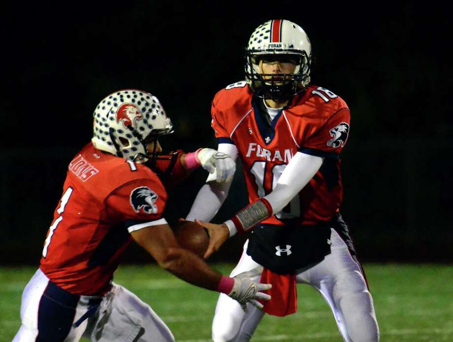 Foran QB Lance DiNatale hands the ball of to Roberto Balado, during high school football action against West Haven in Milford, Conn. on Friday October 23, 2015. Photo: Christian Abraham / Hearst Connecticut Media / Connecticut Post