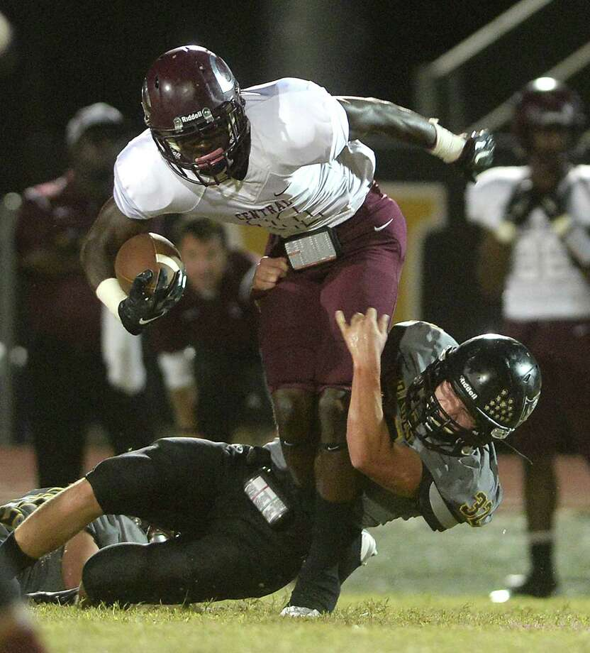 Central's Quentin Derry tries to power through the tackling efforts of Vidor's Jace Baumgarte during Friday night's game at Vidor High School.