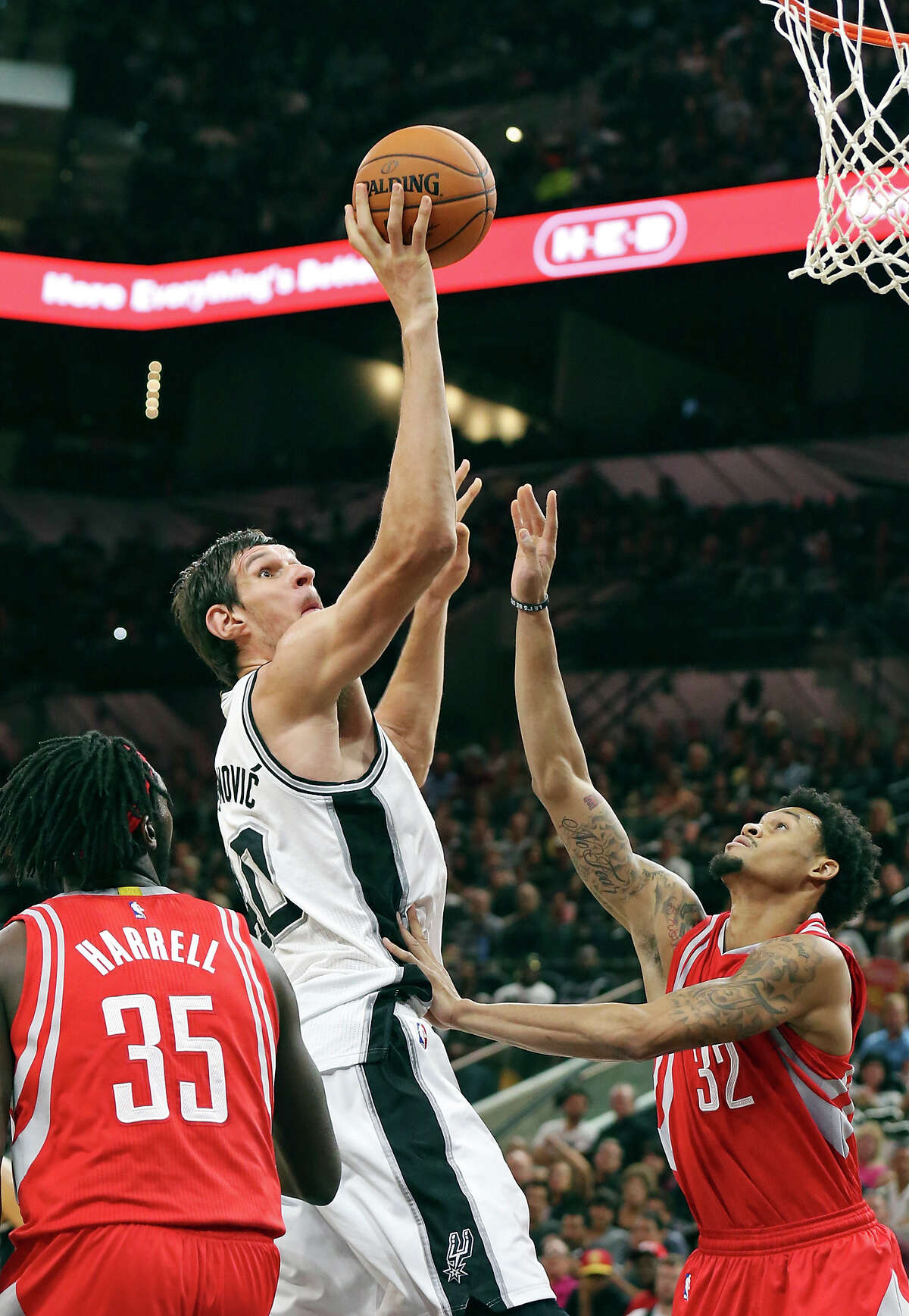San Antonio Spurs' Boban Marjanovic shoots between Houston Rockets' Montrezl Harrell (left) and K.J. McDaniels during second half action Friday Oct. 23, 2015 at the AT&T Center. The Spurs won 111-86.