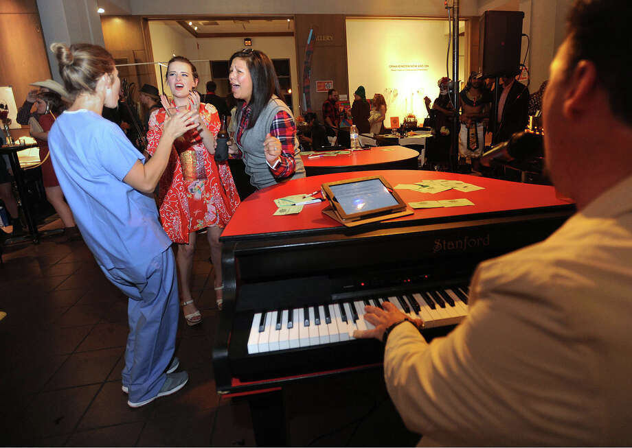 From left, Amanda Pratt, Kelsey Rowe and Jessica Rhodes sing along during the Art Museum of Southeast Texas' Monster Mash fundraiser Friday night. The costumed event offered music, a walk through the galleries and craft beers. Photo taken Friday, October 23, 2015 Guiseppe Barranco/The Enterprise Photo: Guiseppe Barranco, Photo Editor