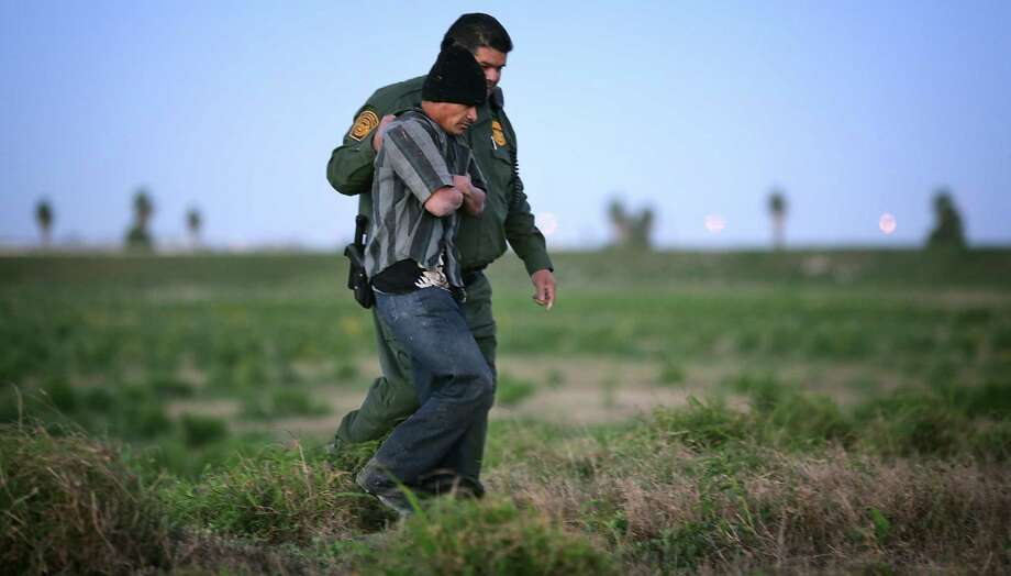 A Border Patrol officer keeps a grip on an un- documented immigrant from Guate- mala near Weslaco. A Border Patrol union official in McAllen testified that President Barack Obama's immigration policies encourage illegal immigration. Photo: Bob Owen /San Antonio Express-News / ©2013 San Antonio Express-News