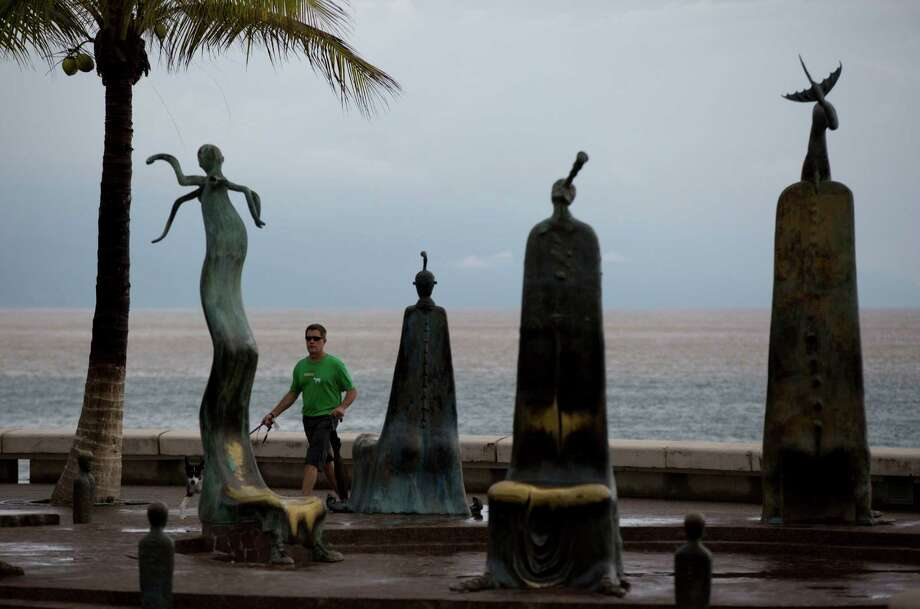 A man walks his dogs along the seafront the morning after Hurricane Patricia passed further south, sparing Puerto Vallarta, Mexico, Saturday, Oct. 24, 2015.  The storm made landfall Friday evening on Mexico's Pacific coast as a  Category 5 hurricane with maximum sustained winds of 165 mph (270 kph) but it is rapidly losing steam as it moves over a mountainous region inland from the shore. Photo: Rebecca Blackwell, AP / AP