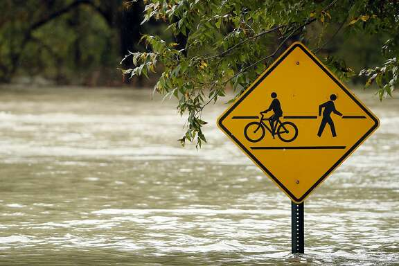 A bicycle and walking path is flooded by White Rock Lake after heavy rain fall soaked the region Friday, Oct. 23, 2015, in Dallas. Residents braced for more rain this weekend from other storms that could spin off from massive Hurricane Patricia approaching southwest Mexico.  (AP Photo/Tony Gutierrez)
