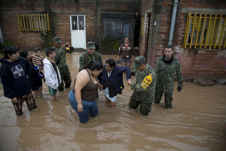 Soldiers help a woman to leave her flooded house to take her to a shelter in Zoatlan, Nayarit state, some 150 km northwest of Guadalajara,  Mexico, Saturday, Oct. 24, 2015. Hurricane Patricia made landfall Friday on a sparsely populated stretch of Mexico's Pacific coast as a Category 5 storm, avoiding direct hits on the resort city of Puerto Vallarta and major port city of Manzanillo as it weakened to tropical storm force while dumping torrential rains that authorities warned could cause deadly floods and mudslides. (AP Photo/Eduardo Verdugo) Photo: Eduardo Verdugo, Associated Press