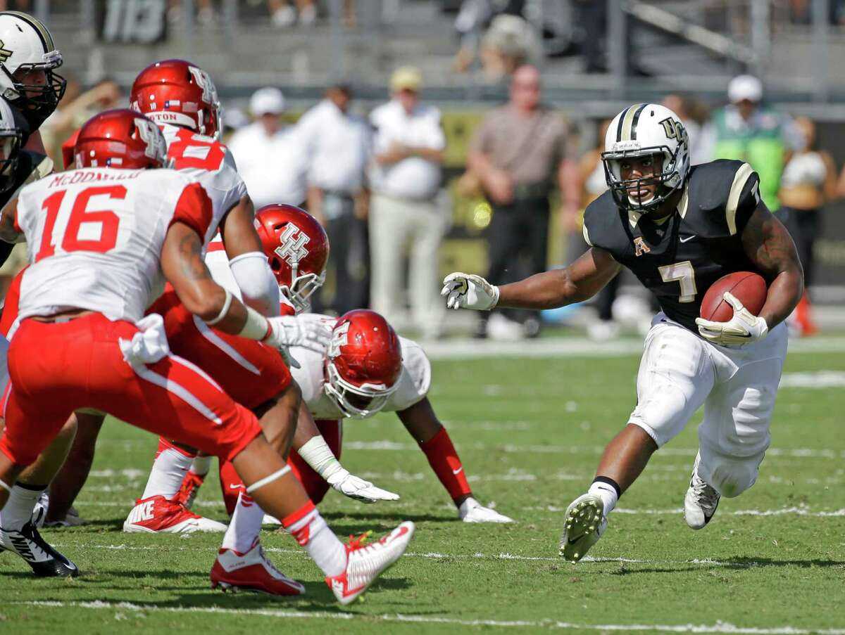 Central Florida running back Dontravious Wilson (7) looks for an opening past Houston safety Adrian McDonald (16) and other defenders during the first half of an NCAA college football game, Saturday, Oct. 24, 2015, in Orlando, Fla. (AP Photo/John Raoux)