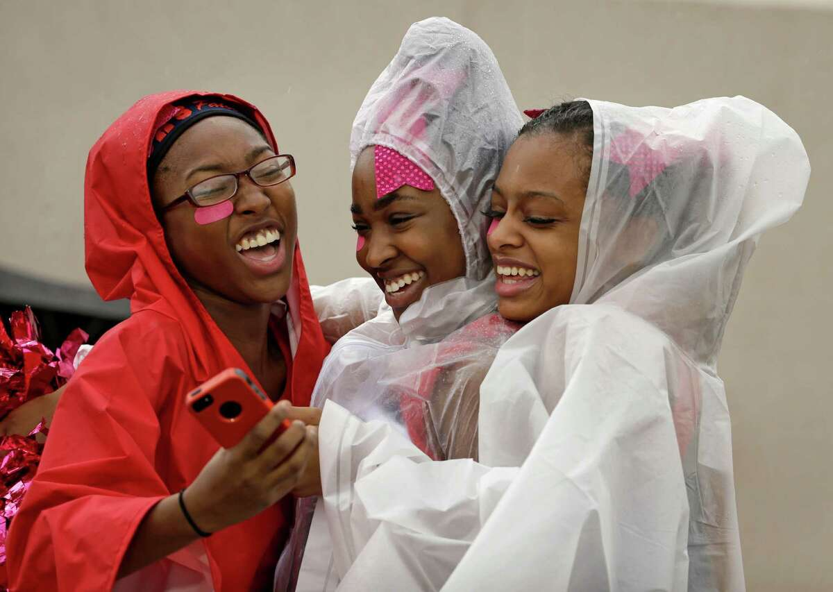 Davis H.S. seniors Natyria Newkirk, 17, left, Kendall Muse, 17, center, and Celeste Barrett, 18, right, laugh as they take a selfie photo during the rainy game against Eisenhower H.S. at W.W. Thorne Stadium Saturday, Oct. 24, 2015, in Houston.