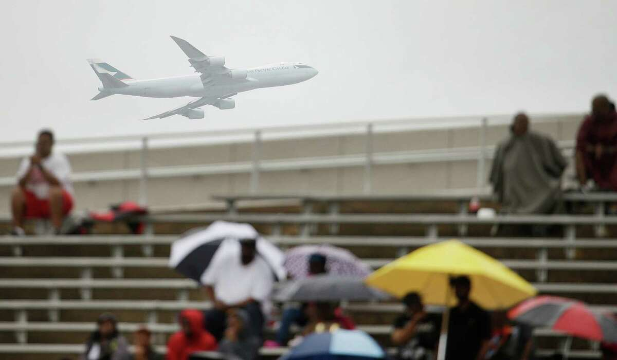 An airliner is shown departing from George Bush Intercontinental Airport as fans brave the rainy weather in the stands during the Davis H.S. and Eisenhower H.S. football game at W.W. Thorne Stadium Saturday, Oct. 24, 2015, in Houston.