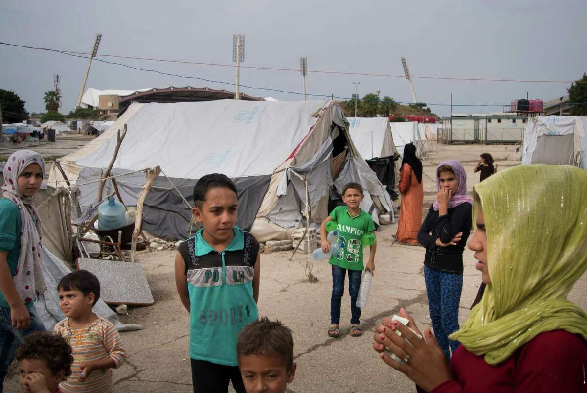 In this photo taken on Friday, Oct. 23, 2015, Refugees stand at a camp in Latakia, Syria. Take a look at how many Syrian refugees call each American state home.