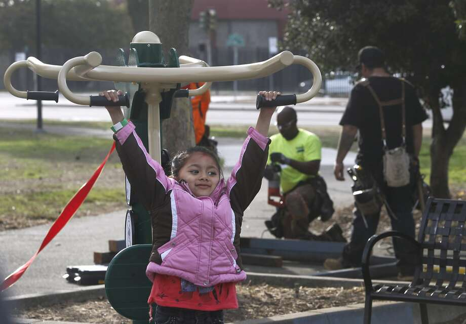 Ashwini Palikhe, 5, tries out the new exercise equipment while volunteers rebuild and refurbish John F. Kennedy Park behind her in Richmond, Calif. on Saturday, Oct. 24, 2015. Photo: Paul Chinn, The Chronicle