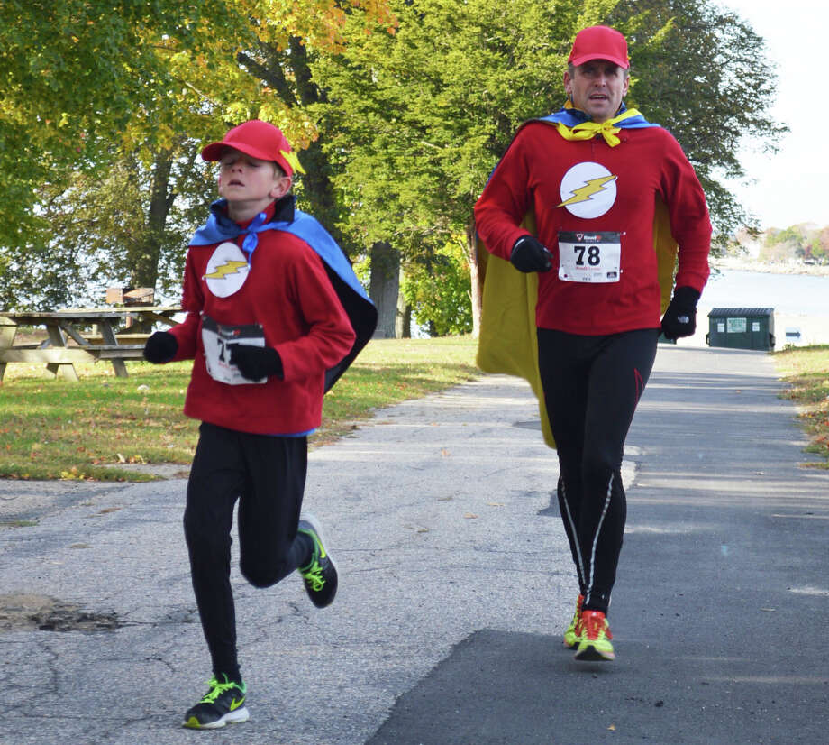 Dressing as the speedy Flash may have helped improve the time for Patrick McCarthy of Wilton and his son Aidan, 9, in Saturday's Ghost & Goblin 5K Walk/Run at Sherwood Island State Park. Photo: Jarret Liotta / For Hearst Connecticut Media / Westport News