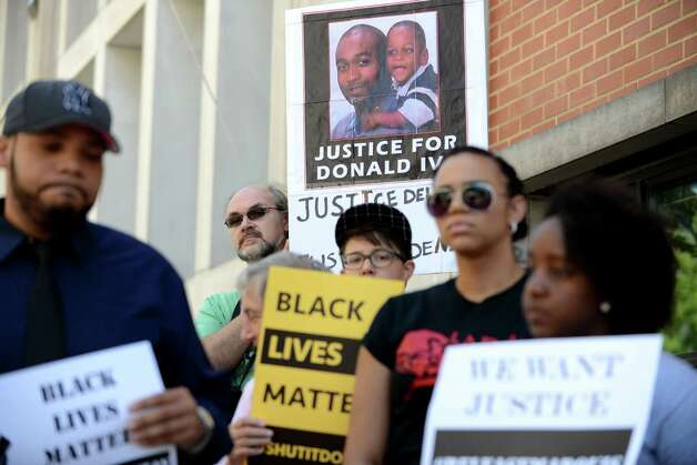 "Demonstrators hold signs in support of Marquis Dixon and ""Dontay"" Ivy during a press conference and rally outside Albany District Attorney David Soares' office Monday, Aug. 10, 2015, in Albany, N.Y. Advocates called on the district attorney to publicly call the nine-year sentence teen Marquis Dixon received for stealing sneakers excessive and to support Raise the Age legislation that has awaits action by the state Legislature next year. They also called on him to finish an investigation into the police-related death of Donald ""Dontay"" Ivy, deliver indictments against the three officers involved and publicly support the use of a special prosecutor in cases of police killings of civilians. (Will Waldron/Times Union) Photo: WILL WALDRON / 00032956A"