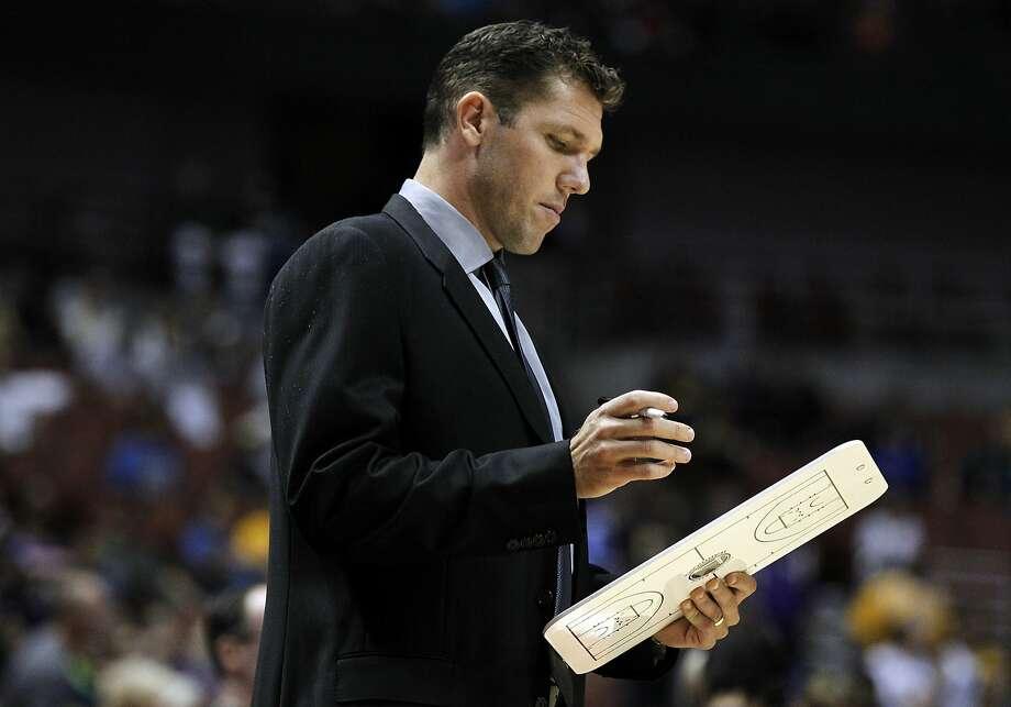 Warriors interim head coach Luke Walton looks over his notes in the first half of a preseason game Thursday against the Los Angeles Lakers in Anaheim. Photo: Alex Gallardo, Associated Press