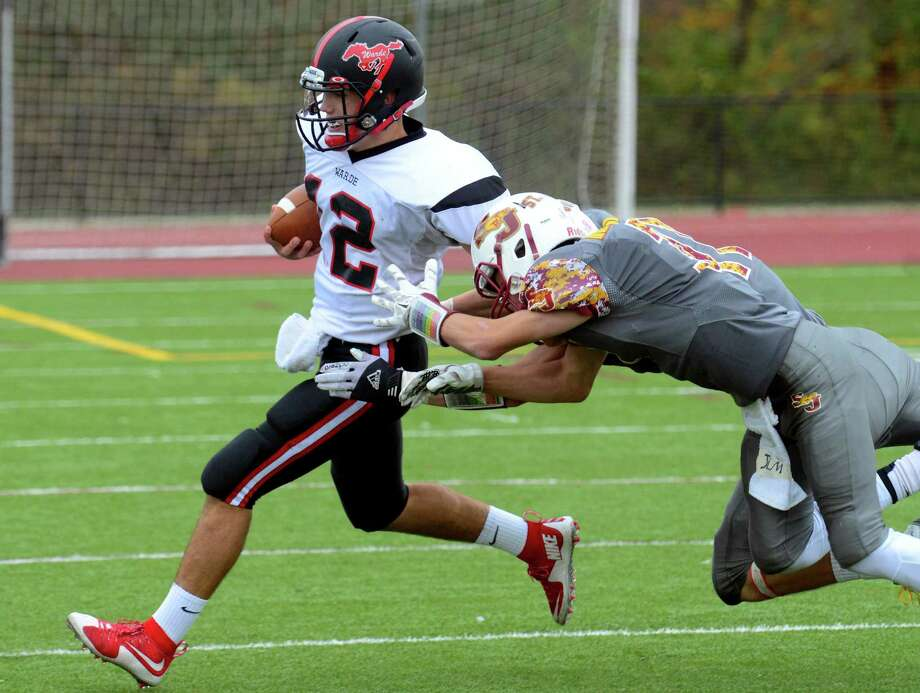 Fairfield Warde QB Jack Potenza tries to shake St. Joseph's Jared Mallozzi and Cameron Ryan during high school football action in Trumbull, Conn. on Saturday October 24, 2015. Photo: Christian Abraham / Hearst Connecticut Media / Connecticut Post