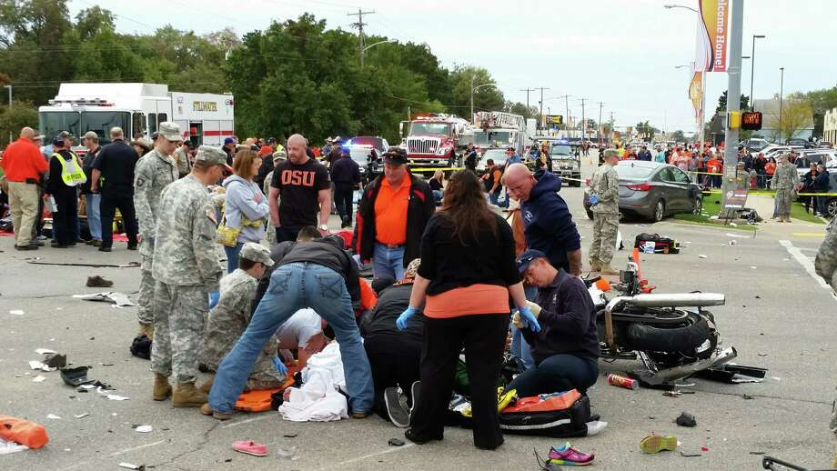 Emergency personnel and spectators respond after a vehicle crashed into a crowd of spectators during the Oklahoma State University homecoming parade, causing multiple injuries, on Saturday, Oct. 24, 2015 in Stillwater, Oka.  (David Bitton/The News Press via AP) MANDATORY CREDIT Photo: David Bitton, MBO / Associated Press / The News Press