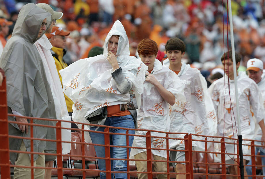 Longhorns fans cover up for rain that lasts the whole game as UT hosts Kansas State at Royal-Memorial Stadium in Austin on Oct. 24, 2015. Photo: Tom Reel /San Antonio Express-News