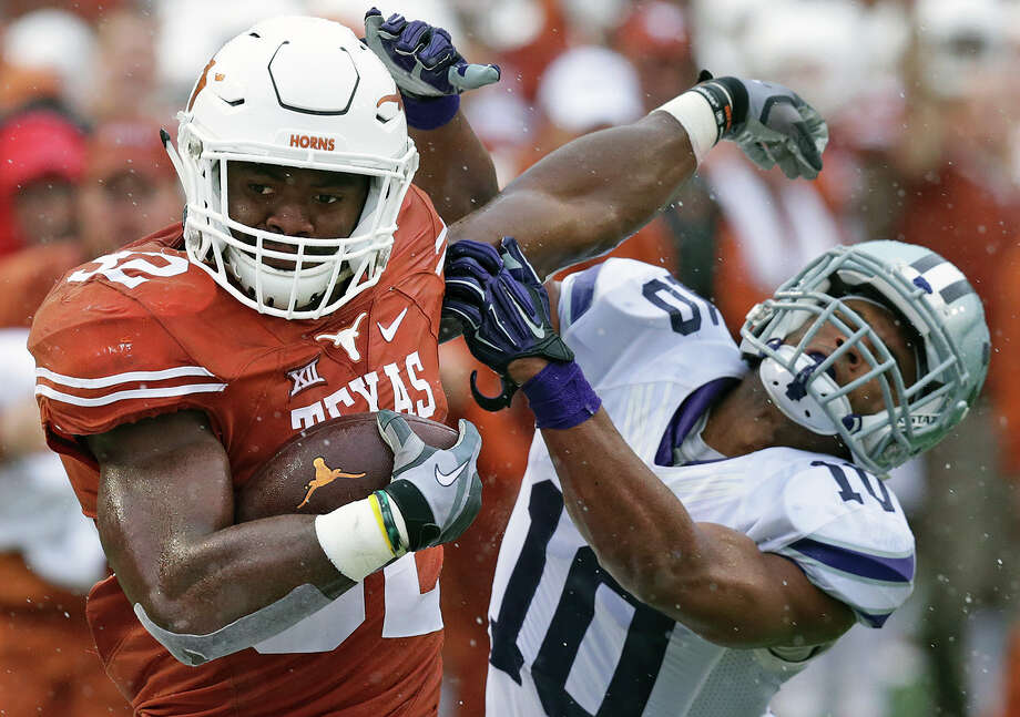 UT running back Johnathan Gray fends off Kansas State's Donnie Starks, who forces him out of bounds after a long gain in the first half at Royal-Memorial Stadium in Austin on Oct. 24, 2015. Photo: Tom Reel /San Antonio Express-News